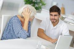 Молодой человек и бабушка работая совместно на компьтер-книжке Стоковое Изображение