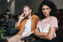 Молодой человек и девушка сидя в ресторане Расстроенная Афро-американская девушка при темное вьющиеся волосы уныло смотря в сторо Стоковое Изображение