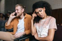 Молодой человек и девушка сидя в ресторане Сердитая Афро-американская девушка при темное вьющиеся волосы уныло смотря в сторону п Стоковые Изображения