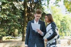 Молодой человек и девушка outdoors смотря документы Стоковые Фото