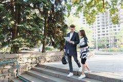 Молодой человек и девушка outdoors смотря документы Стоковая Фотография RF