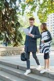Молодой человек и девушка outdoors смотря документы Стоковые Изображения