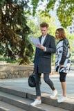 Молодой человек и девушка outdoors смотря документы Стоковые Фотографии RF