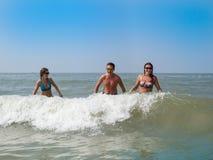 Молодой человек и 2 девушки имеют потеху в море Лето, остатки, жара Стоковая Фотография