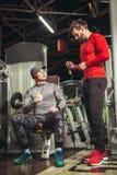 Молодой человек и его личный тренер фитнеса в спортзале Стоковое фото RF