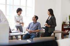 Молодой человек и 2 женских коллеги говоря в офисе Стоковые Фотографии RF
