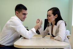 Молодой человек и женщина воюют на его руках на столе в офисе для босса места, головы Сражение сексов, молодое hav пар Стоковая Фотография RF