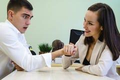 Молодой человек и женщина воюют на его руках на столе в офисе для босса места, головы Сражение сексов, молодое hav пар Стоковая Фотография