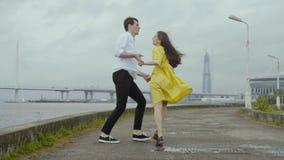 Молодой человек и женщина в желтых танцах платья переплетают около реки в городе видеоматериал
