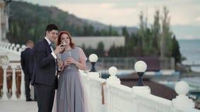 Молодой человек и женщина в платье вечера и костюм на обваловке около моря Гости на партии торжества видеоматериал