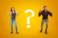 Молодой человек и женщина в случайных одеждах показывая сомнение с большим вопросительным знаком на желтой предпосылке стоковое фото