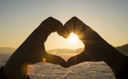 Молодой человек и женщина делая сердце формируют с ее пальцами стоковое фото