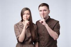 Молодой человек и женщина держа их пальцы на губах спрашивая быть молчаливый стоковое изображение