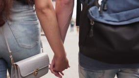 Молодой человек и женщина держа руки и идут совместно на городскую улицу акции видеоматериалы