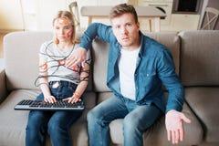 Молодой человек и женщина имеют социальную наркоманию средств массовой информации o Заложники Бесчувственная женщина на софе Потр стоковые изображения
