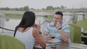 Молодой человек и женщина имея обед в ресторане на открытой террасе сток-видео