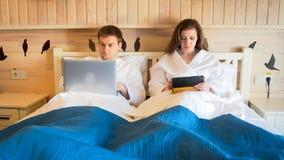 Молодой человек и женщина лежа в кровати на гостинице и работая на компьтер-книжке и таблетке Стоковые Изображения RF