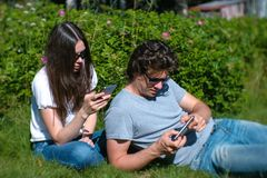 Молодой человек и женщина пар имея остатки в парке, смотря и играя на мобильном телефоне стоковое изображение rf