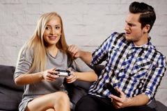 Молодой человек и женщина сидят на кресле и играют игру Стоковое Фото