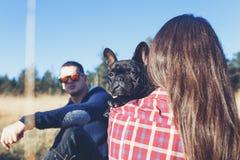 Молодой человек и женщина с их собакой outdoors стоковые изображения