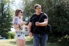 Молодой человек и женщина с рыболовной удочкой на реке в Германии Стоковые Фотографии RF