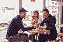 Молодой человек и 2 женщины сидя на таблице в кафе ходят по магазинам Стоковое Изображение RF