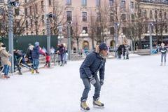 Молодой человек катаясь на коньках на общественном катке катания на коньках outdoors в городе Стоковые Фото