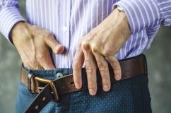 Молодой человек кладет на пояс в брюки закрывает вверх стоковые фотографии rf