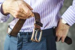 Молодой человек кладет на пояс в брюки закрывает вверх стоковая фотография rf