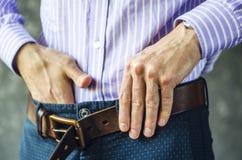 Молодой человек кладет на пояс в брюки закрывает вверх стоковые изображения