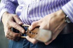 Молодой человек кладет на пояс в брюки закрывает вверх стоковое фото rf