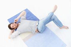 Молодой человек кладя на пол используя передвижной усмехаться Стоковые Фото