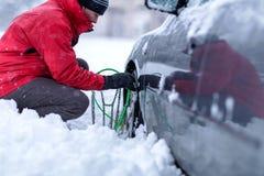 Молодой человек кладя цепи зимы на автомобиль стоковое изображение rf