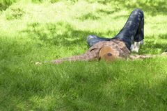 Молодой человек лежа и ослабляя на зеленой траве стоковое изображение
