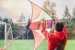Молодой человек летая змей на футбольном поле Стоковая Фотография