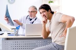 Молодой человек навещая старый мужской радиолог доктора стоковые изображения rf