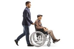 Молодой человек нажимая пожилого человека в кресло-коляске стоковые фотографии rf