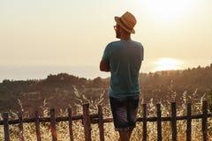 Молодой человек наслаждаясь заходом солнца морем Стоковые Фотографии RF
