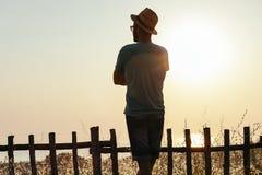Молодой человек наслаждаясь заходом солнца морем Стоковые Изображения RF