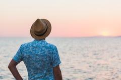 Молодой человек наслаждаясь заходом солнца морем Стоковая Фотография RF