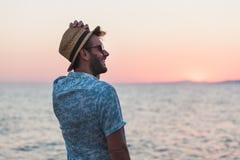 Молодой человек наслаждаясь заходом солнца морем Стоковое Изображение