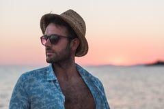 Молодой человек наслаждаясь заходом солнца морем Стоковое Изображение RF