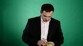Молодой человек находит деньги в книге Зеленая предпосылка видеоматериал