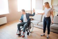 Молодой человек на кресло-коляске спорит с девушкой Инвалидность и всесторонний Человек с особенными потребностями Расстроенный и стоковая фотография