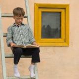 Молодой человек на лестнице читает книгу на солнечном после полудня Стоковая Фотография RF