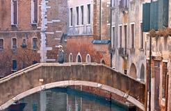 Молодой человек на небольшом старом мосте между былыми зданиями в узком канале воды и фасадом исторических зданий в задней части стоковые изображения
