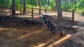 Молодой человек на покатом курсе горного велосипеда в древесинах Стоковое Изображение