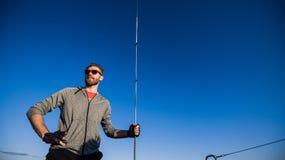 Молодой человек на положении катамарана и веревочка удержания перед голубым небом во время курсировать стоковая фотография rf