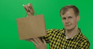 Молодой человек на предпосылке зеленого chroma экрана ключевой с хозяйственной сумкой стоковое изображение rf