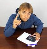 Молодой человек на столе с чалькулятором Стоковые Изображения RF